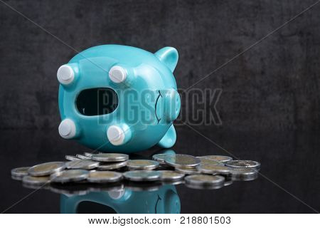 Saving money problem with empty piggy bank lay on dark black table with coins using as broke or personal financial crisis.