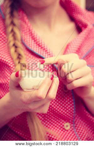 Young woman wearing red dotted pajamas applying moisturizing skin cream with her finger. Jar with lotion in female hands. Girl taking care of dry complexion layering moisturizer. Skincare treatment
