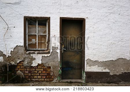 Broken windows and the crooked door of a dilapidated residential building.