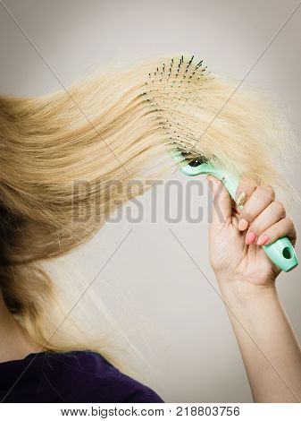 Everyday hygiene and care about good look. Blonde girl combing her long straight hair. Woman using green comb hairbrush.