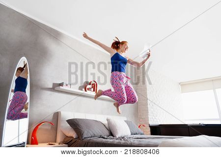 Happy young latina woman jumping mid air on bed, hispanic girl smiling and laughing in bedroom after reading good news on paper letter.