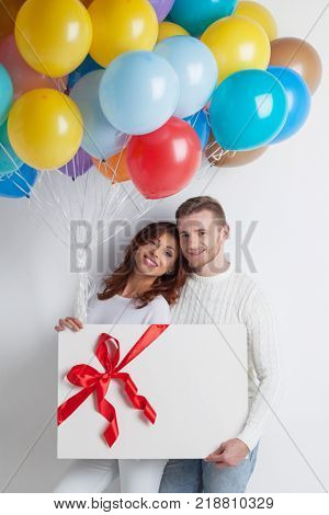 Young smiling couple with balloons and big gift box