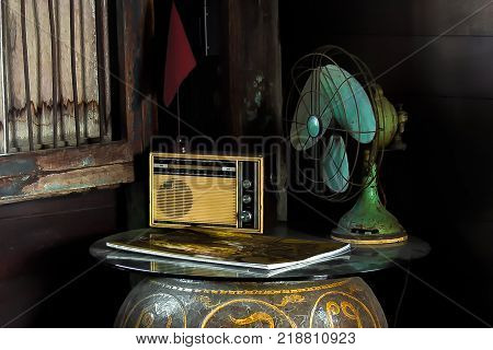 Still Life with vintage household appliances. Composition of an old transistor radio, electric oscillating fan, magazine, and red banner placed on glass top with a large glazed clay pot base.