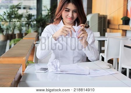 Frustrated young Asian employee holding crumpled paper and feeling stress against her job in office.