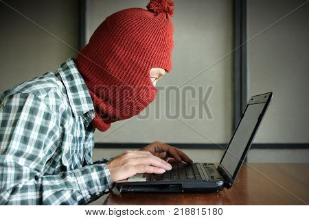 Side view of masked hacker wearing a balaclava looking a laptop and stealing important information data. Network security and privacy crime concept.