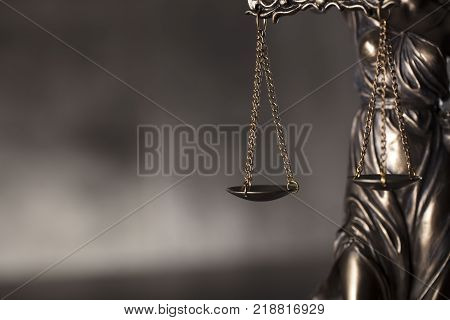Courtroom concept. Themis - blind justice. Gray stone background. Place for typography.