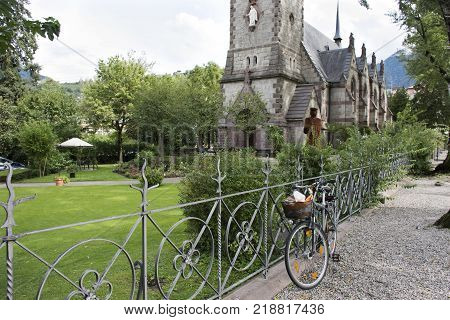 Travelers people stop bicycle and visit relax at garden of Chiesa evangelica di Cristo church at walkway riverside passer river in Meran city in Merano Italy