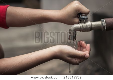 Child reach out waiting for water Water shortage concept.