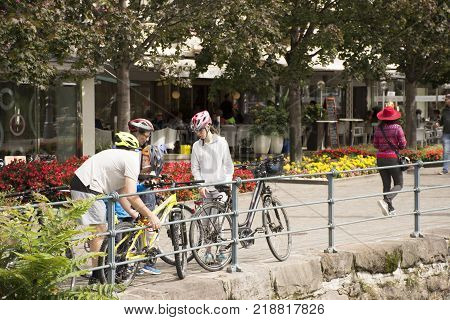 Italian People And Foreigner Travelers Stop Bicycle And Walking On The Footpath At Riverside Of Pass
