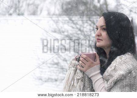 Woman drinking hot beverage under snowfall - Portrait of a beautiful young brunette woman covered with a handmade shawl drinking a cup of hot coffee outdoor while snowing.