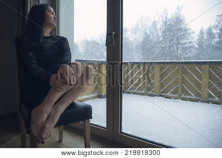 Woman relaxing in front of window while snowing - Beautiful woman wearing a sexy black dress sits on a chair with her eyes closed in front of big glass doors while outside is snowing abundantly.