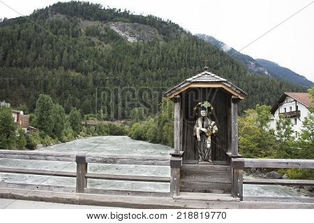 St. Lukas Statue In Wooden Cottage On Old Bridge Over Bad Inn River At Pfunds Village In Tyrol, Aust