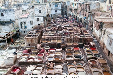FEZ, MOROCCO - JANUARY 4, 2014: Men working hard in the tannery souk in Fez Morocco. The tannery souk of weavers is the most visited part of the 2000 years old city.