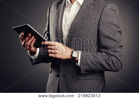 Handsome Young Man in Business Suit. Casual style and Electronic Gadgets. Smart Watches and Digital Tablet