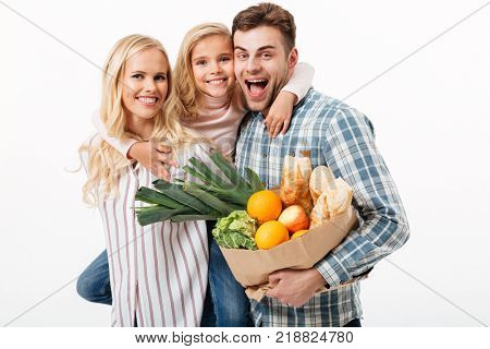 Portrait of a beautiful family holding paper shopping bag full of groceries isolated over white background