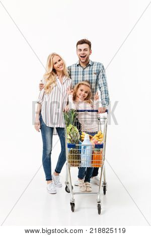 Full length portrait of a lovely family standing with a shopping trolley full of groceries isolated over white background