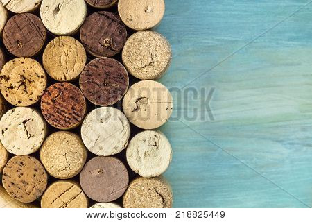 A closeup photo of wine corks, shot from above on a teal background texture with a place for text. A design template for a wine list or a tasting invitation