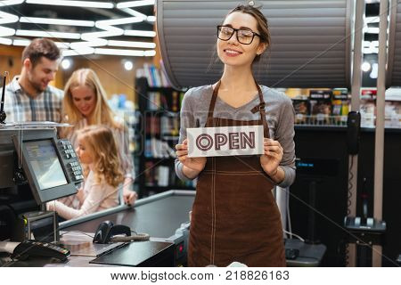 Portrait of friendly woman cashier holding open sign while standing at cash counter in supermarket
