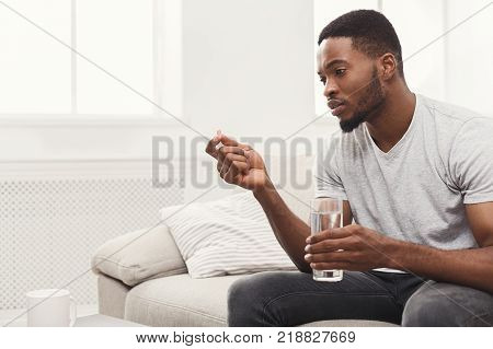 Serious african-american man ready to take a pill sitting on a couch at home, copy space