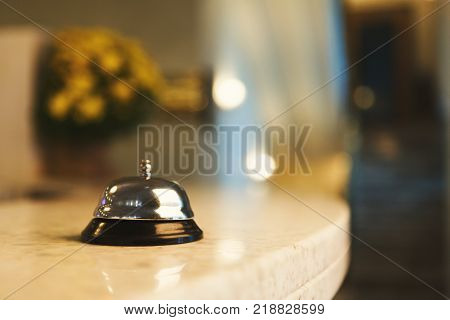 Hotel accommodation call bell on reception desk, contemporary interior, copy space
