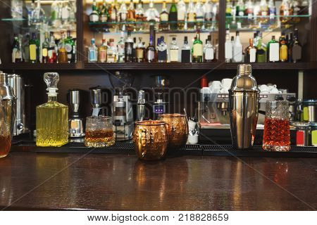 Creative exotic alcohol cocktails assortments on bar counter background, refreshing drinks in public place, copy space