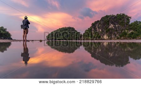 Reflection of man photographer take photo of summer landscape with beautiful sunset sky at Ao Nang Beach famous tourist attraction and travel destination of Krabi Province Thailand