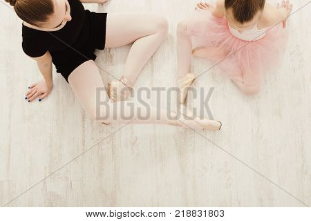 Little girl in ballet studio with teacher copy space. Cute small ballerina sitting on floor with female coach, top view. Classical dance school