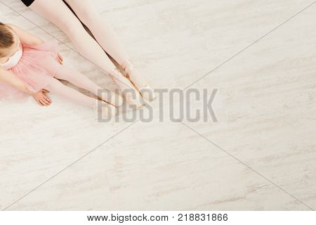 Ballet background. Little girl and young ballerina legs in pointe shoes on white wooden floor, top view from above with copy space. Classical dance school background, practicing for children