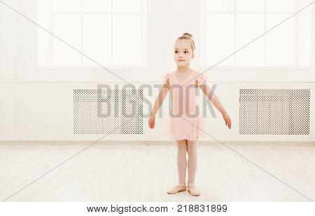 Little ballerina exercising in ballet costume, standing on her toes. Cute small ballerina training classical dance exercisese