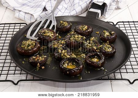 grilled mushroom with chopped garlic and parsley on a pan