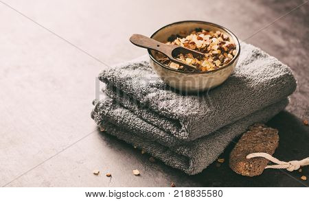 SPA background with towels, bath salts and a natural pumice stone for foot care.