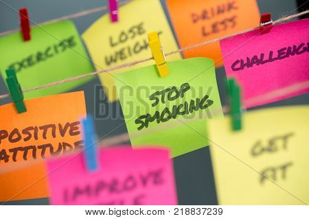 Sticky note with important message stop smoking and slogans hanging on rope with clip