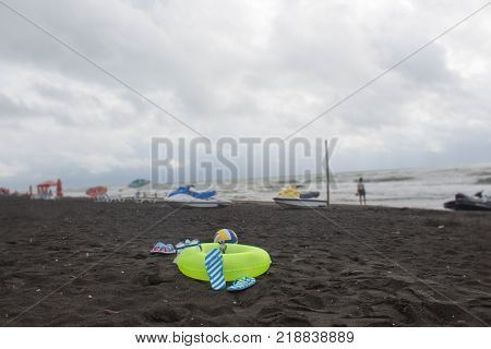 Ball swimming glasses sandal Water scooter and Floating Ring on beach. Blurred people on sand beach overcast surge. Travel or sea vacations concept