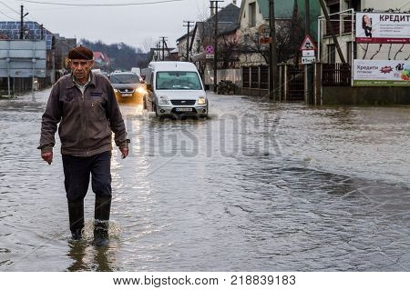 Syltse Ukraine - December 16 2017: The senior man and the cars are moving along the flooded central street during the winter flood in the village of Syltse.