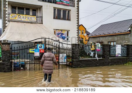 Syltse Ukraine - December 16 2017: The woman goes to a local mini-market through a flooded central street during a winter flood in the village of Syltse.