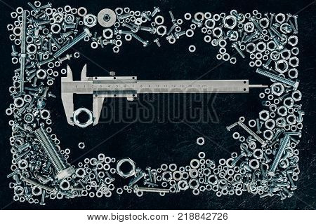 top view of metal vernier caliper, screws and clinchers on dark tabletop