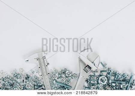 top view of various bolts and framing nails, wrench and vernier caliper set isolated on white