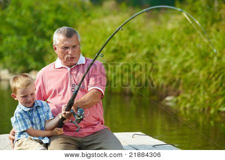 Photo of grandfather and grandson pulling rod together while fishing
