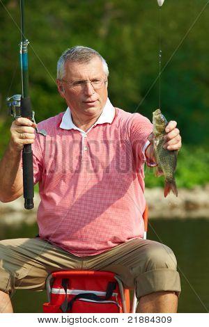 Photo of senior man catching fish on weekend
