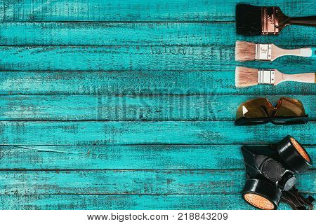 top view of arranged paint brushes, goggles and protective mask for redecoration on blue wooden surface