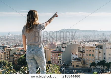 Rear view of young woman wearing in stripped t-shirt standing on high point and looking at cityscape, pointing at something. Summer sunny day, rear view, bird's eye view of city, cityscape, horizon.