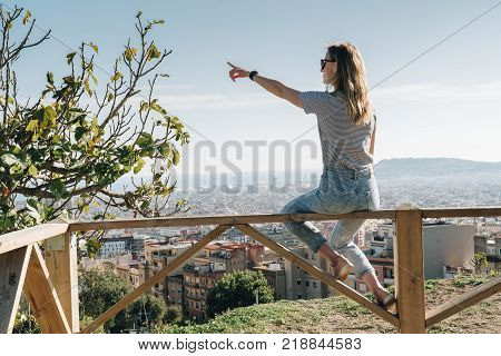 Rear view of young woman wearing in stripped t-shirt sitting on high point and looking at cityscape, pointing at something. Summer sunny day, rear view, bird's eye view of city, cityscape, horizon.