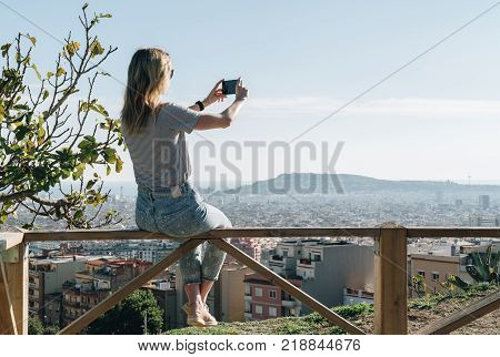 Rear view of young woman wearing in stripped t-shirt and jeans sitting on high point and photographing an urban landscape.Summer sunny day, rear view, view from a bird's eye view of city, city landscape.