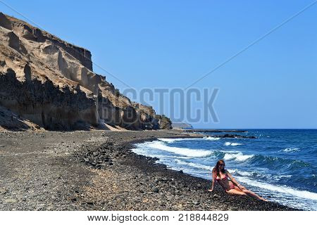 Young woman indark glasses and in red swimsuit sits on dark gray sand/stones of Vourvoulos beach, Santorini, Greece. Background of blue sky and blue sea with waves.