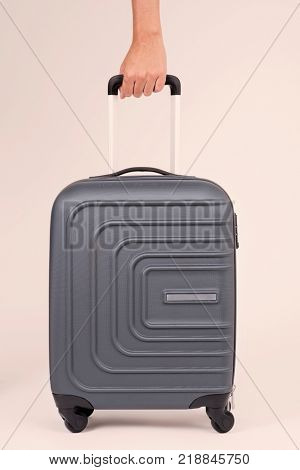 closeup of the hand of a young caucasian man grabbing a trolley case by its handle against an off-white background