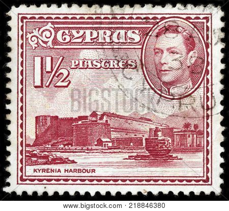 LUGA RUSSIA - OCTOBER 17 2017: A stamp printed by CYPRUS shows image portrait of King George VI and view of Kyrenia - a city on the northern coast of Cyprus circa 1938