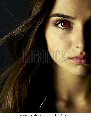 Portrait of beautiful vampire young woman with red eyes.