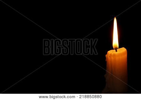 burning wax candle with a wick on a black background in the temple