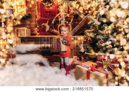 Pretty three year old girl is standing near his house decorated for Christmas and holding a gift box. Time for miracles. Merry Christmas and Happy New Year.