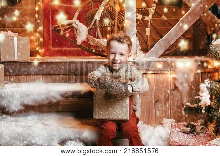 Cute child boy is sitting near his house decorated for Christmas and holding a gift. Time for miracles. Merry Christmas and Happy New Year.